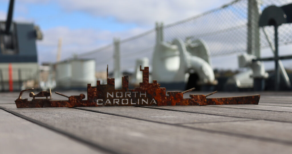 """Battleship-shaped silhouette cut from steel taken from the Ship's hull. The words """"NORTH CAROLINA"""" are cut from the middle."""