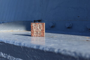"""Square cut from steel taken from the hull of Battleship NORTH CAROLINA with """"BB55"""" inscribed"""