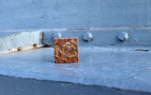 """Square cut from steel taken from the hull of Battleship NORTH CAROLINA with the letters """"NC"""" inscribed"""