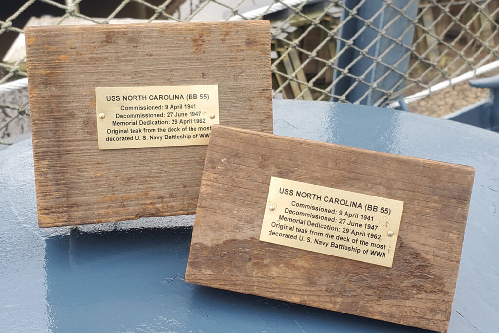 Two sections of original teak pictured on Battleship NORTH CAROLINA. Attached plaque reads: USS NORTH CAROLINA (BB-55) / Commissioned: 9 April 1941 / Decommissioned: 27 June 1947 / Memorial dedication: 29 April 1962 / Original teak from the deck of the most decorated U.S. Navy Battleship of WWII
